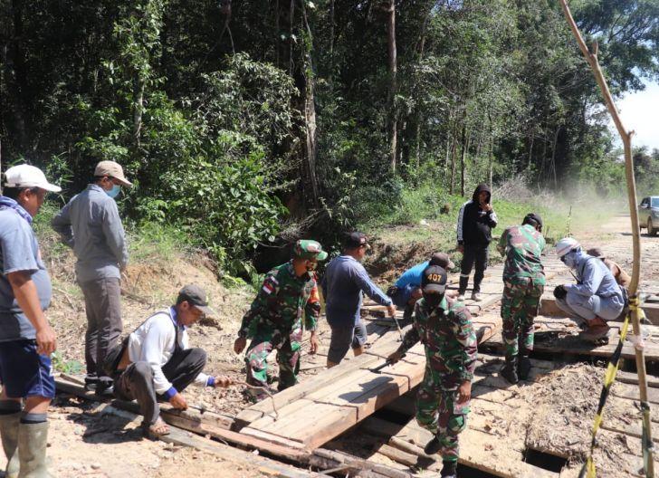 Photo of Semangat Gotong-Royong, Satgas Pamtas Yonif 407/PK Bersama Warga Perbaiki Jembatan