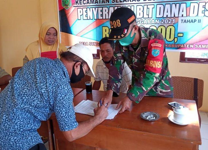Photo of Kawal Pembagian BLT-DD, Babinsa Sai Nyirih Terapkan Protkes
