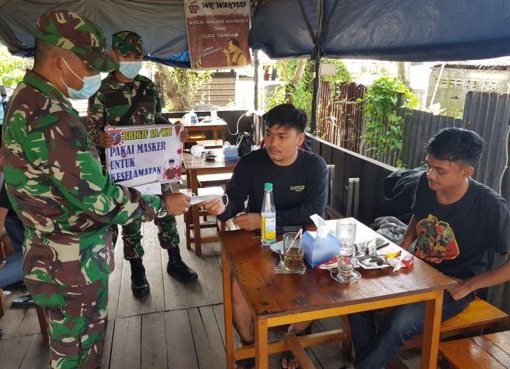 Photo of Personel Brigif Sosialisasi Prokes dengan Bagikan Masker di Warung